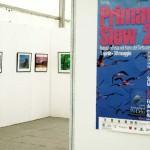 Poster dedicato alla fiera e sullo sfondo la mostra fotografica.
